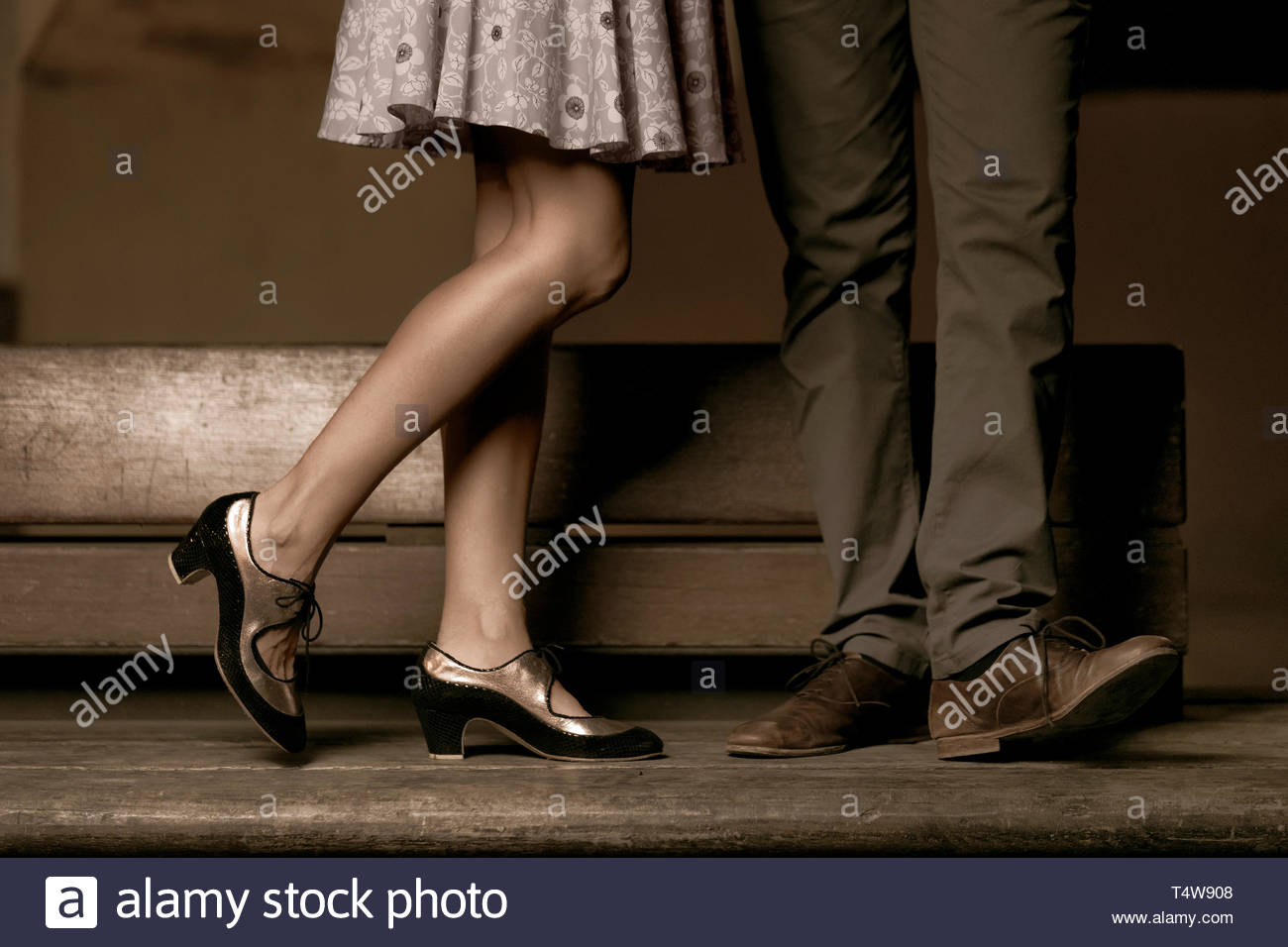 Legs of a couple standing and kissing on a wooden bench. - Stock Image