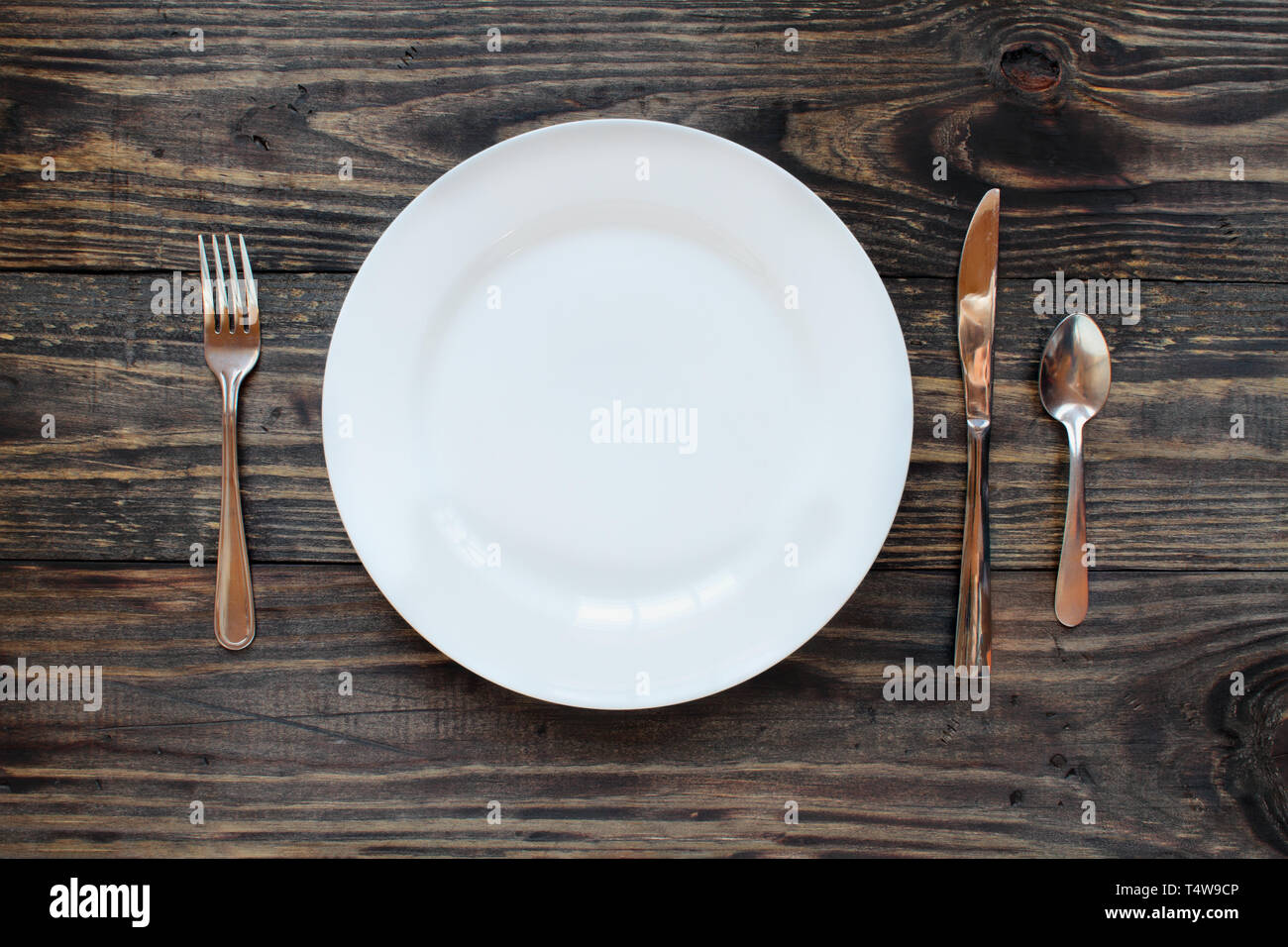 Empty White Dinner Plate Over A Rustic Wooden Table Background With Fork Knife And Spoon Top View Stock Photo Alamy