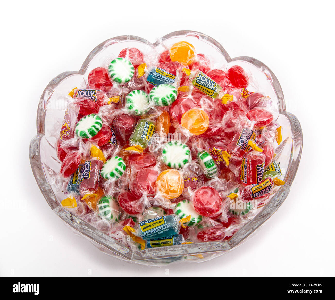 A cut glass bowl with individually wrapped hard candies - Stock Image