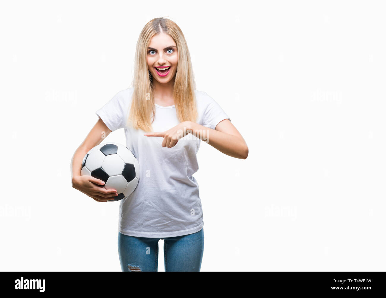 803cc1af0 Young beautiful blonde woman holding soccer ball over isolated background  very happy pointing with hand and finger