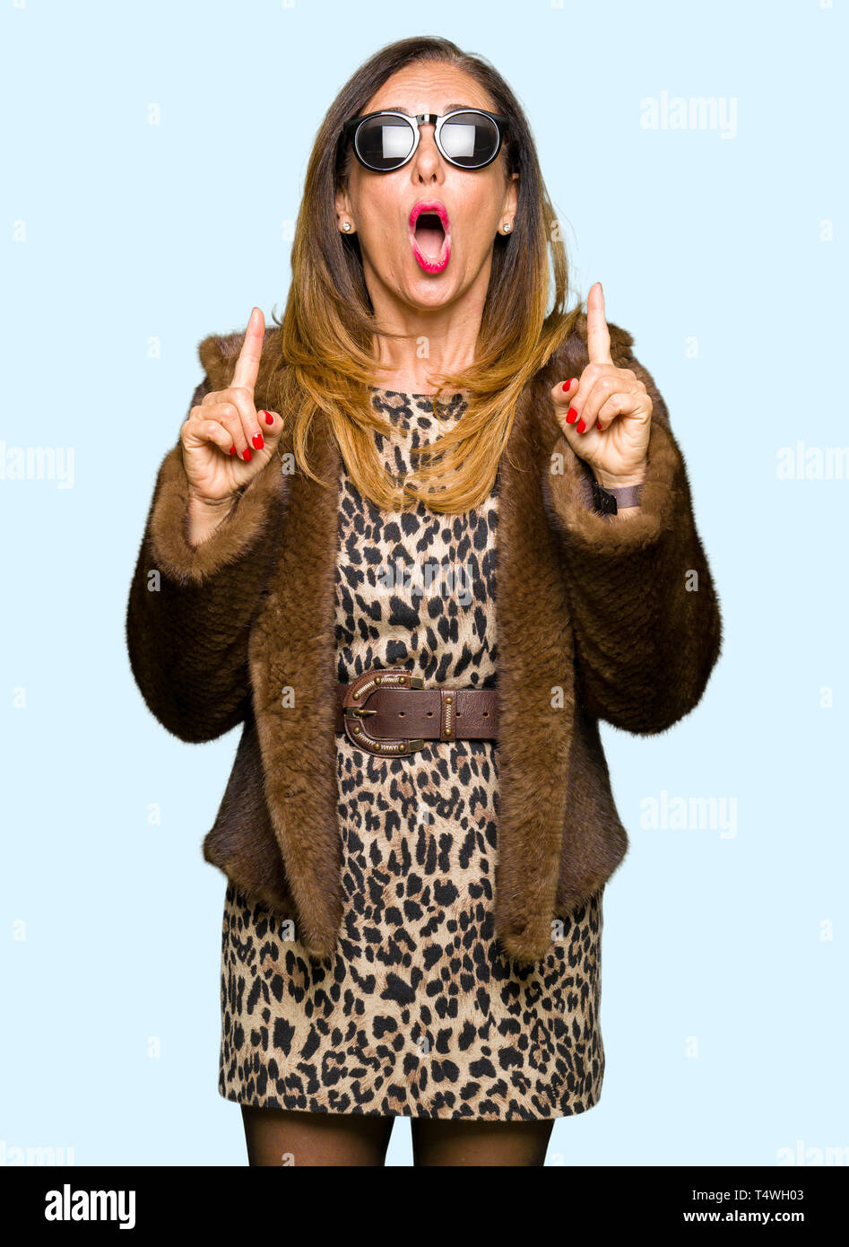 Beautiful middle age elegant woman wearing sunglasses and mink coat amazed and surprised looking up and pointing with fingers and raised arms. Stock Photo