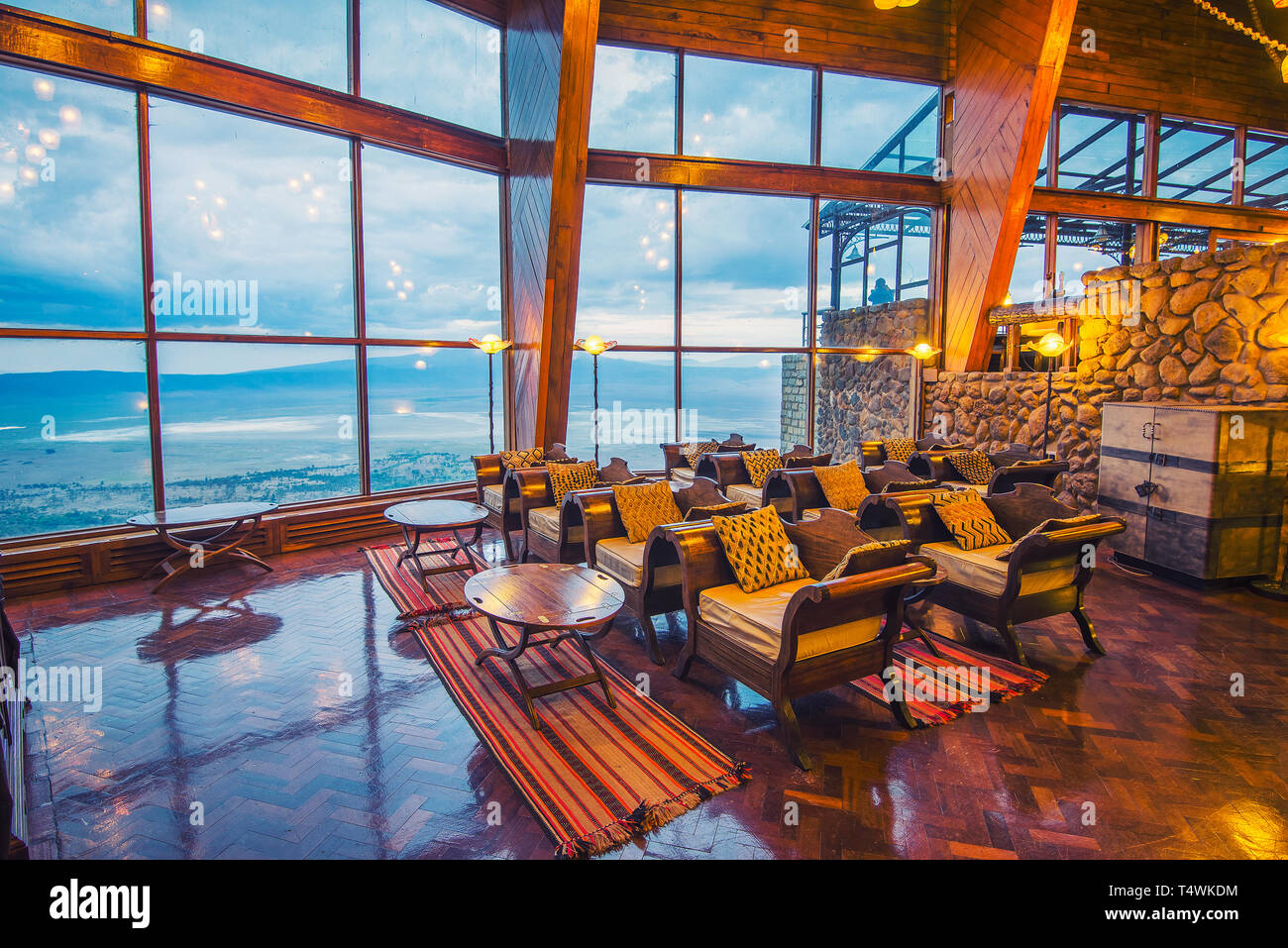 Interior of the Ngorongoro Wildlife Lodge with a glass wall overlooking the park - Stock Image
