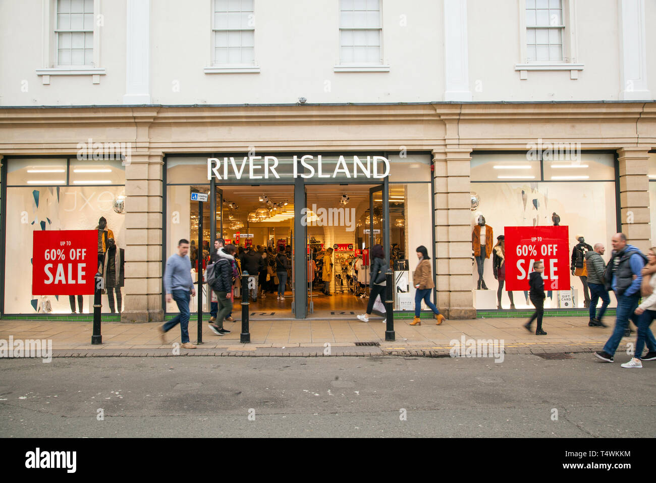 Shoppers walking past the high street  fashion clothes  shop retailer River Island in the town of Cheltenham Gloucestershire England UK Stock Photo