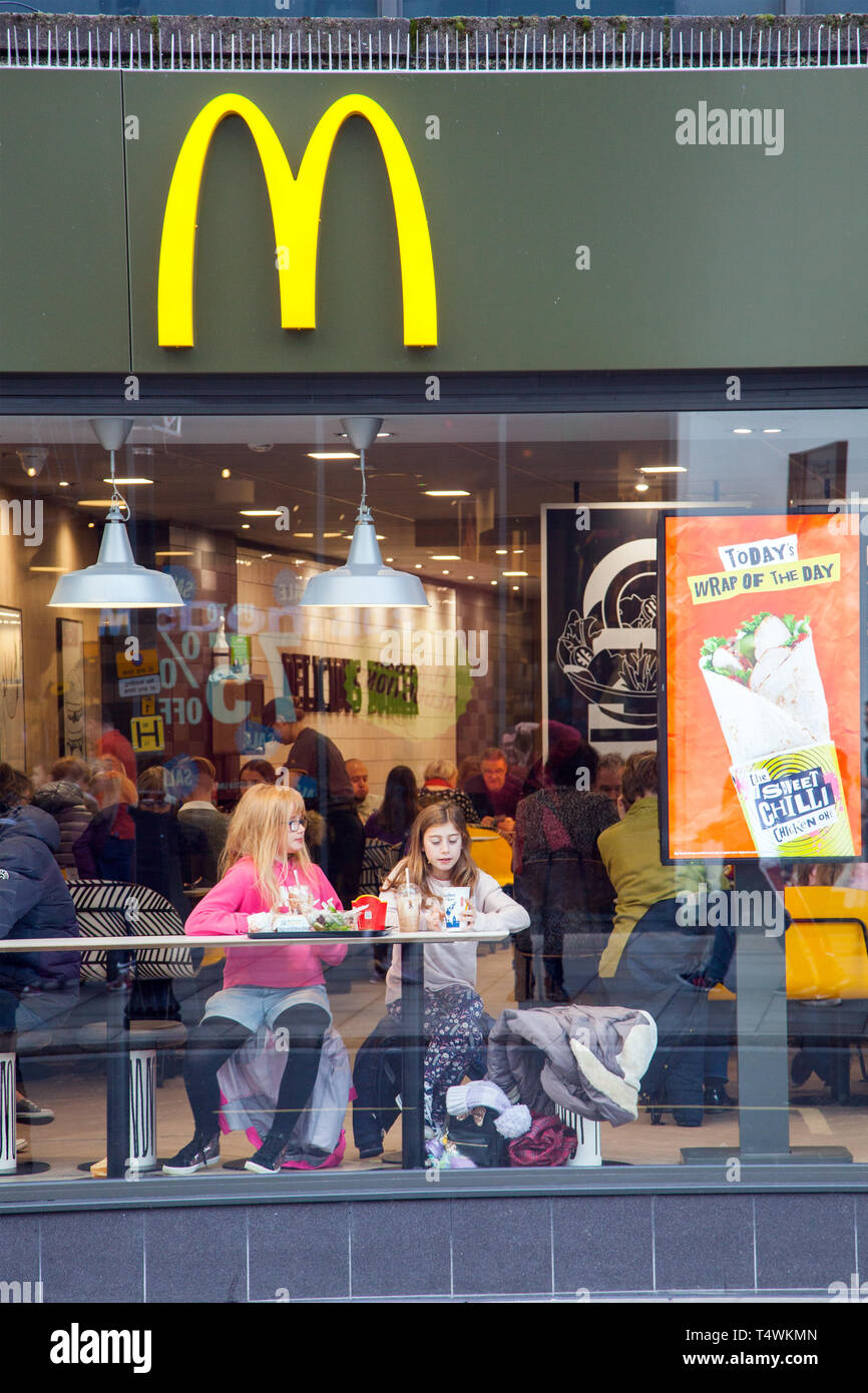 Two young girls sitting eating food and drink in the window of fast food outlet McDonald's in their high street shop - Stock Image
