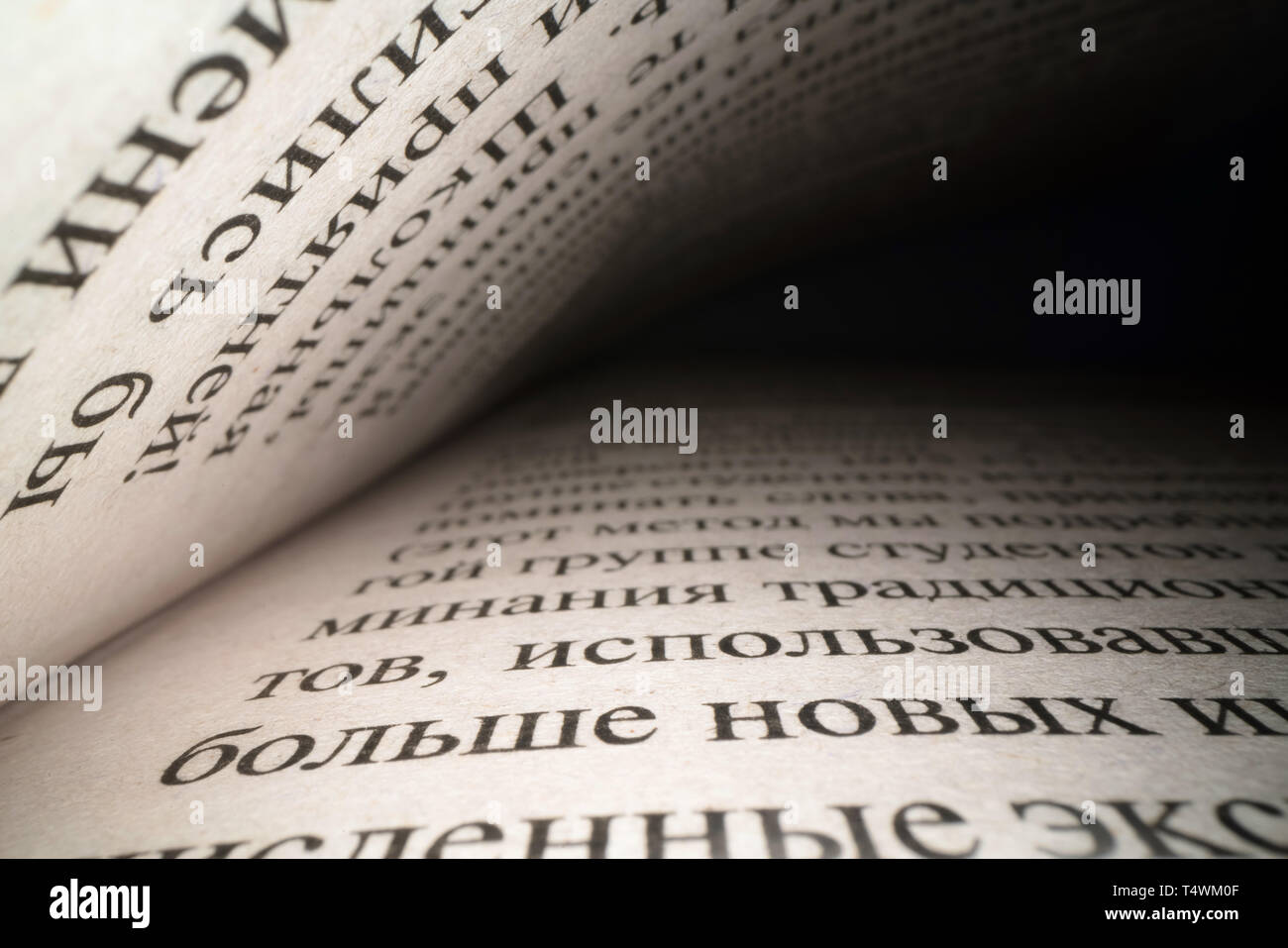 Inside the book concept. Cyrillic letters and words on an open book with black dramatic background. Education, knowledge concept, russian letters - Stock Image