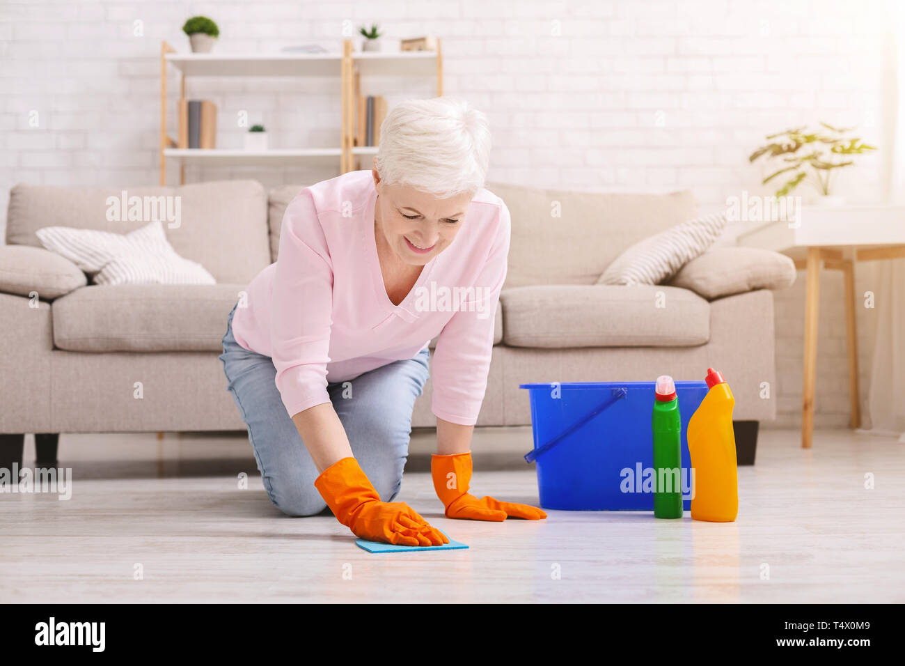 Smiling mature housewife cleaning floor at home - Stock Image