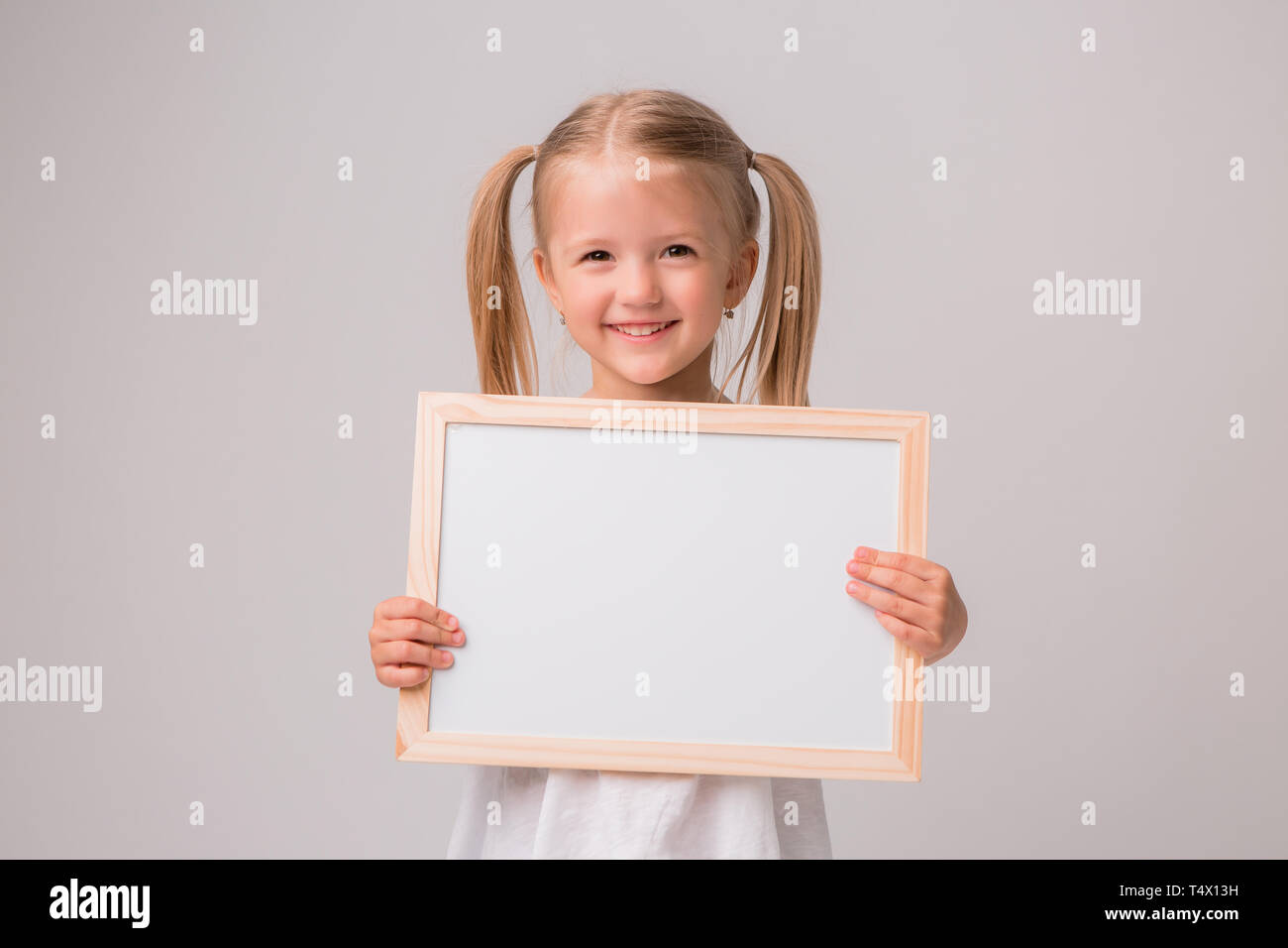 Portrait Of Baby Girl Holding White Drawing Board On White