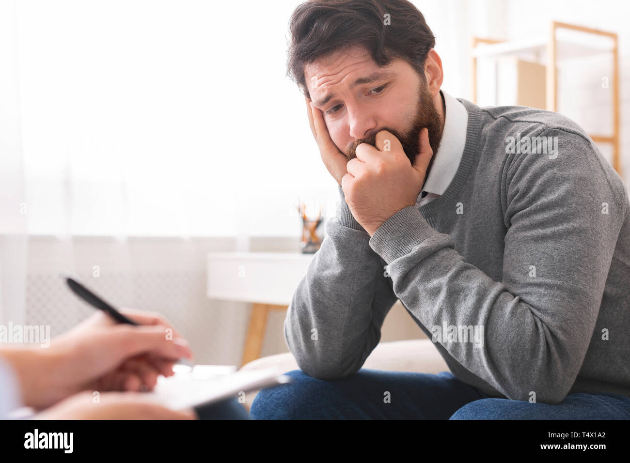Millennial man with depression during psychotherapy session - Stock Image