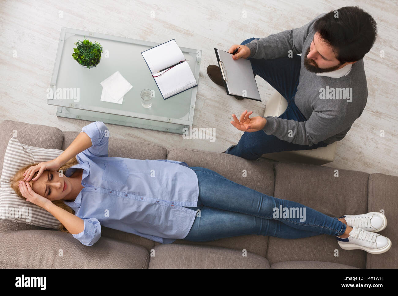 Desperate woman crying, talking to psychologist at therapy session Stock Photo