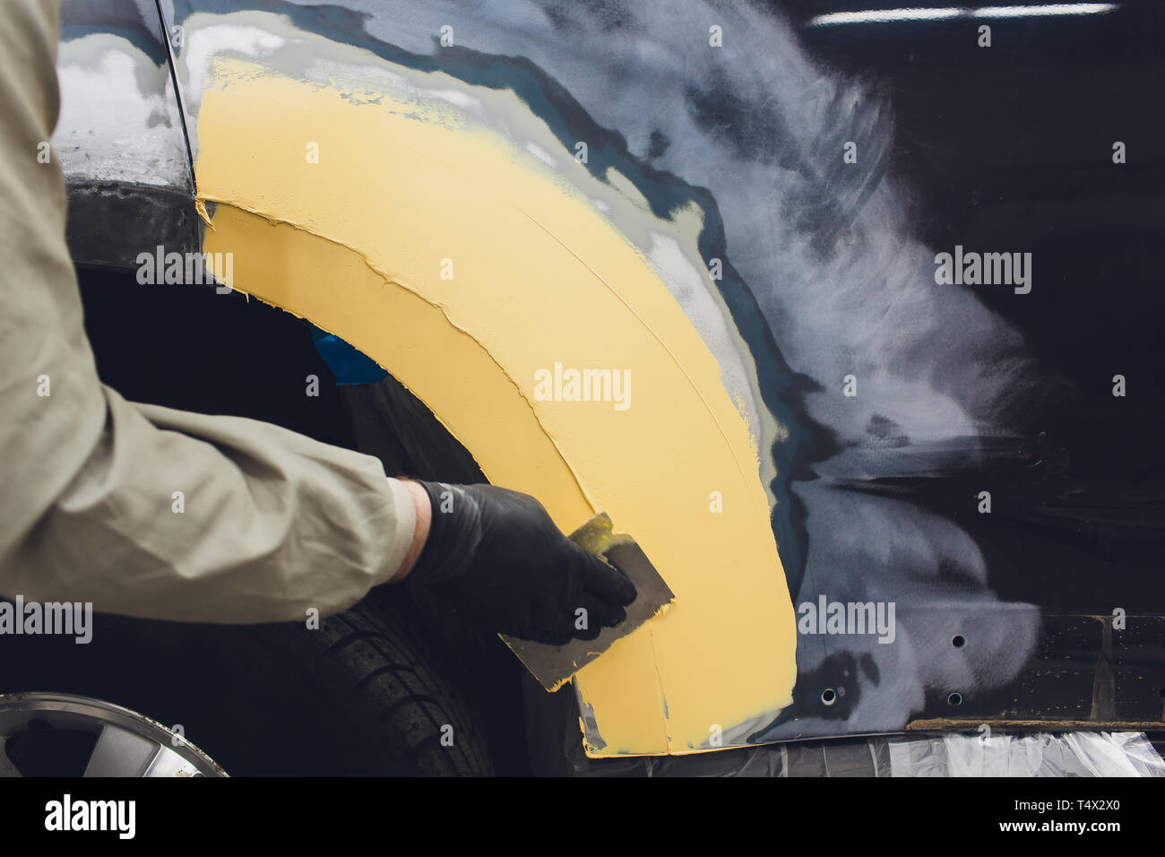Preparation for painting a car element using emery sender a service technician leveling out before applying a primer after damage to a part of the bod - Stock Image