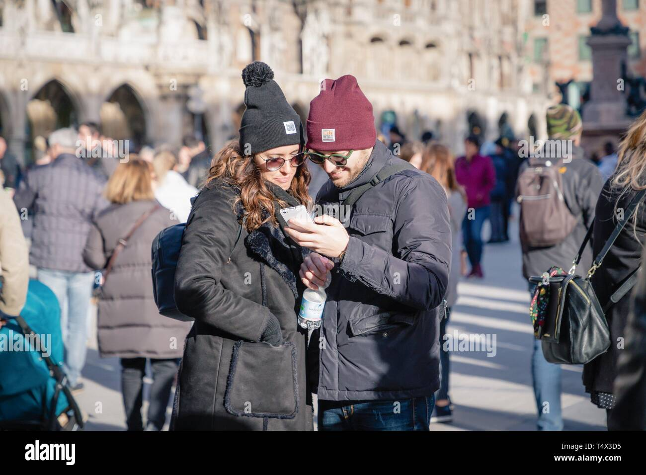 Munich, Germany. February 17, 2019.Beautiful young happy couple looking at smartphone display in the city center - Stock Image