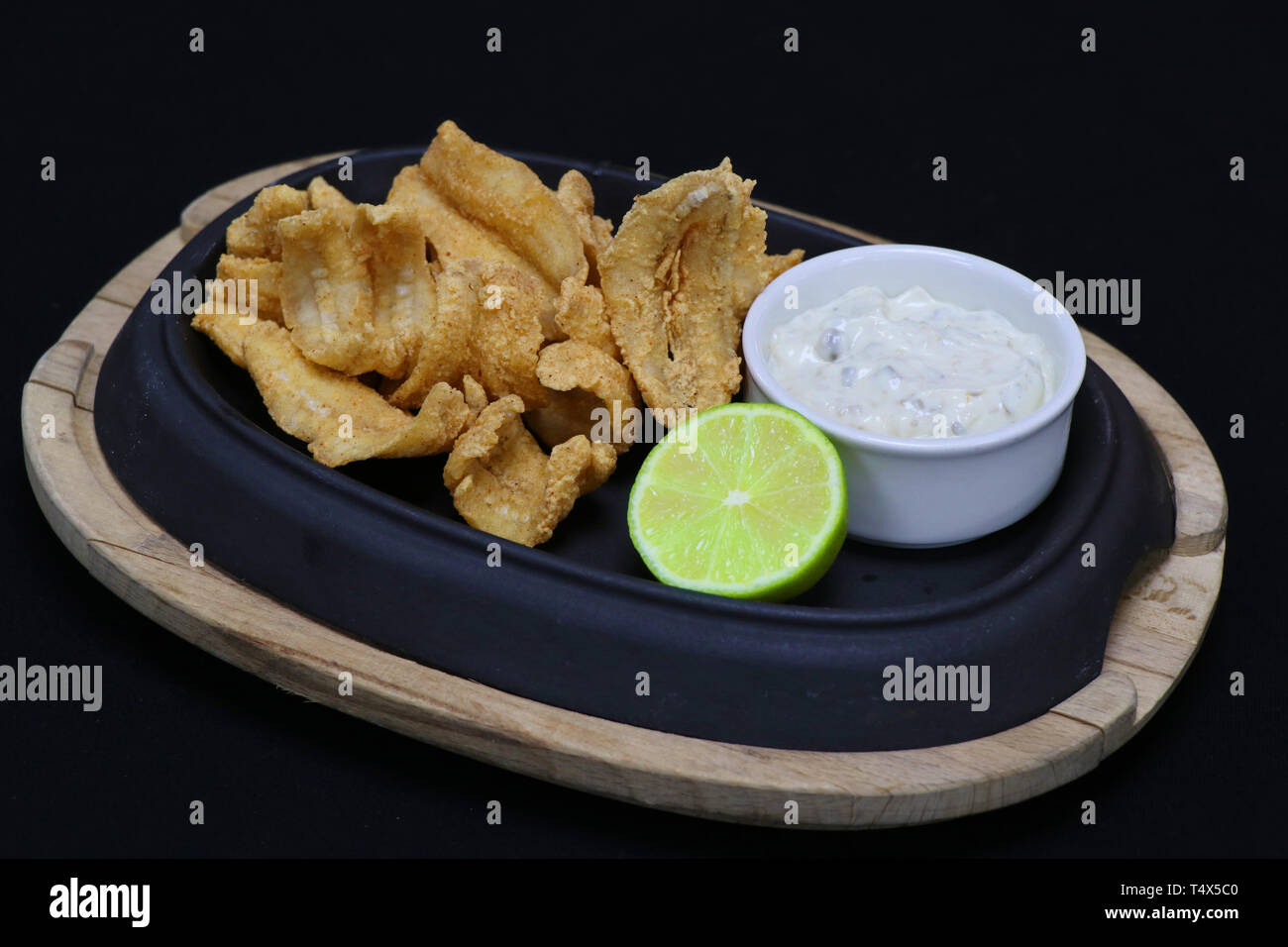 deep fried anchovies with tartar sauce and lime wedge in a serving dish - Stock Image