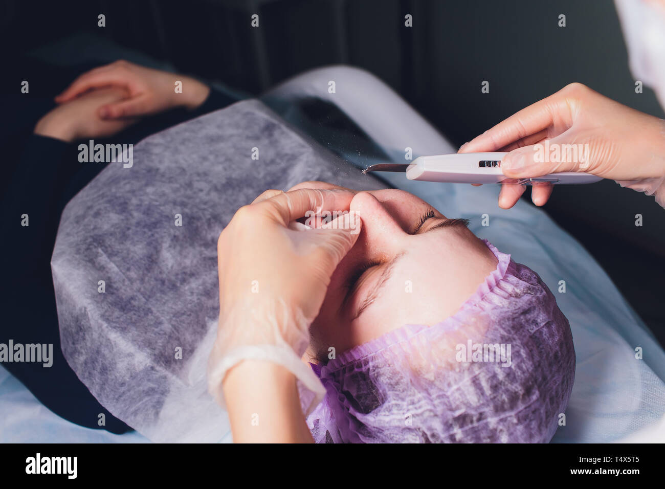 Hardware cosmetology. Beautician makes chromotherapy ultrasound cleaning the client's face. Skin pore cleansing. Anti-aging treatments. Spa. Non - Stock Image