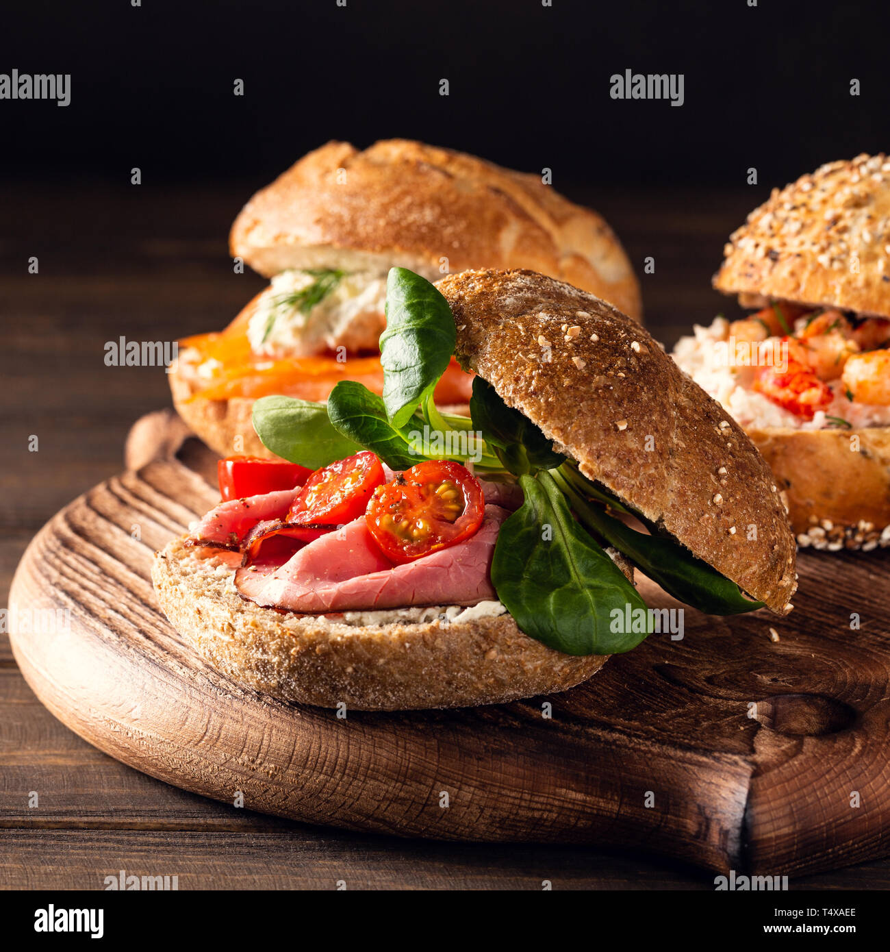 Sandwiche with beef, fresh tomatoes and lamb's lettuce, multigrain bun. Healthy lunch concept with copy space - Stock Image