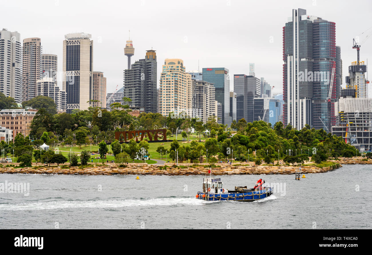 A working boat passes Baragaroo Reserve in Sydney Harbour, with the Sydney skyline behind. Stock Photo