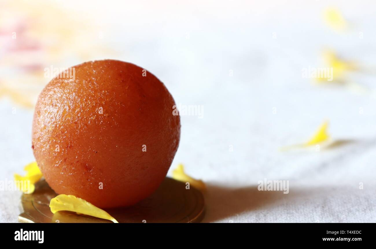 Close-up of a single Gulab Jamun/Indian dessert against white background - Stock Image
