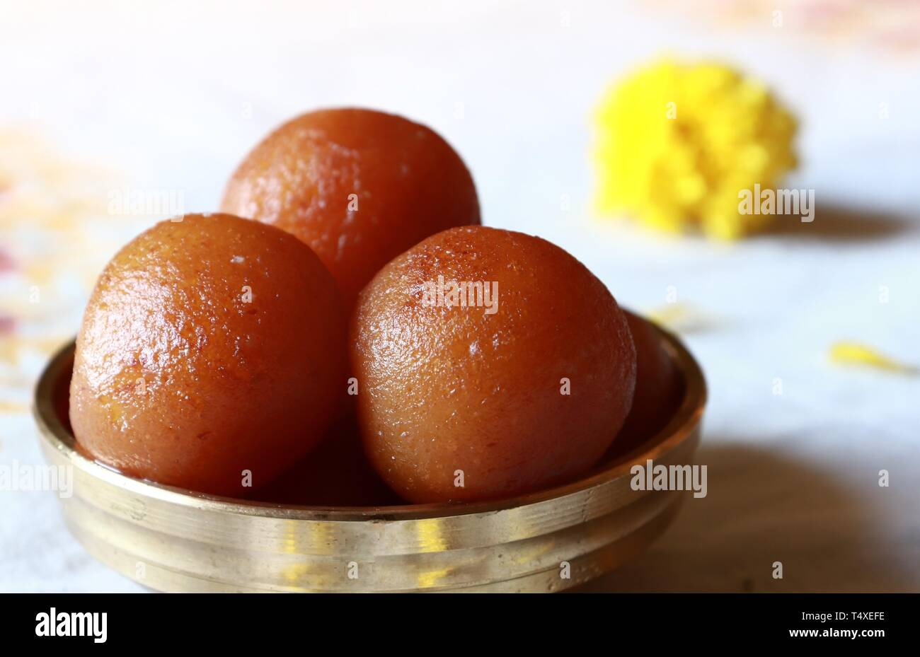 Close-up of Gulab Jamun/Indian dessert in a brass bowl against white background - Stock Image