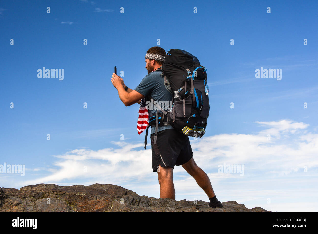 Male backpacker hiking on Appalachian Trail, taking photo with smart cell phone, Great Smoky Mountains National Park, outside Gatlinburg, TN, USA Stock Photo
