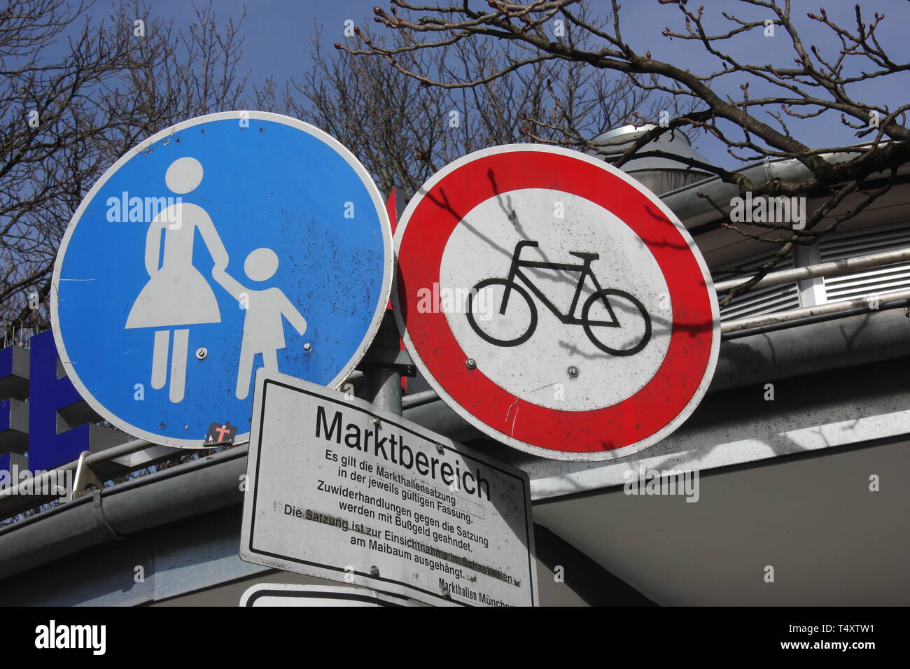Mandatory sign beside prohibition sign. Pedestrians allowed, bicylces forbidden. Road signs in pedestrian area. - Stock Image