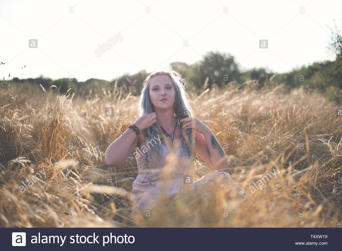 Woman sits in tall grass - Stock Image