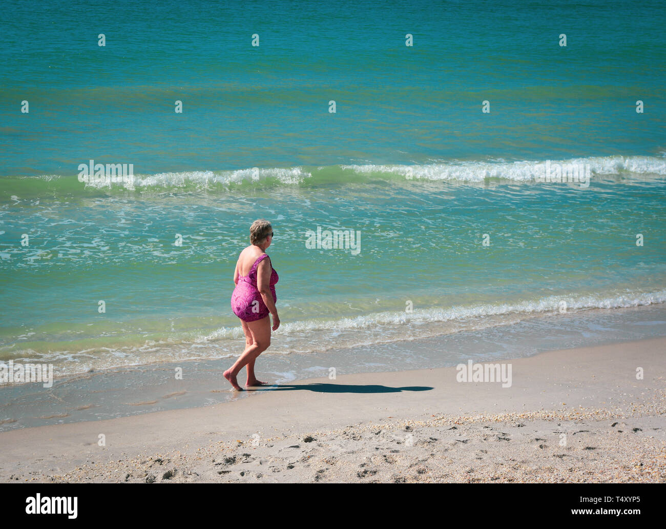 A rear side view of an Older woman wearing a fuschia print bathing suit strolling the water's edge at the beach in Boca Grande, FL, on Gasparilla - Stock Image