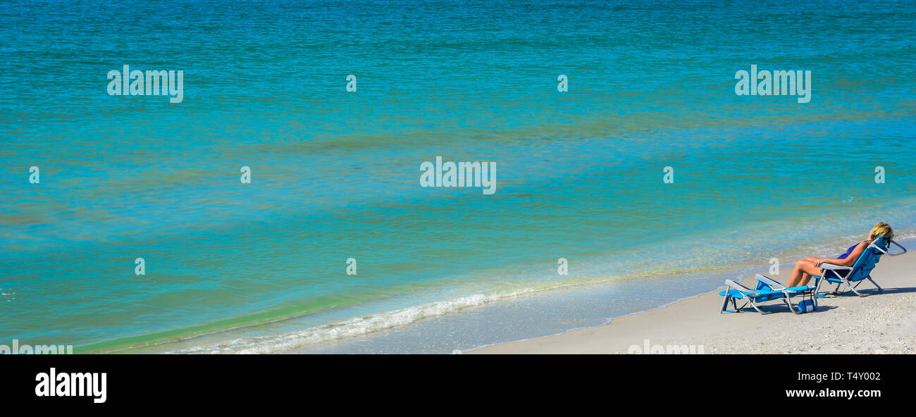A blond woman relaxes in beach chair alongside the seashore with gentle waves lapping nearby with an expanse of turquoise water in a panoramic format - Stock Image