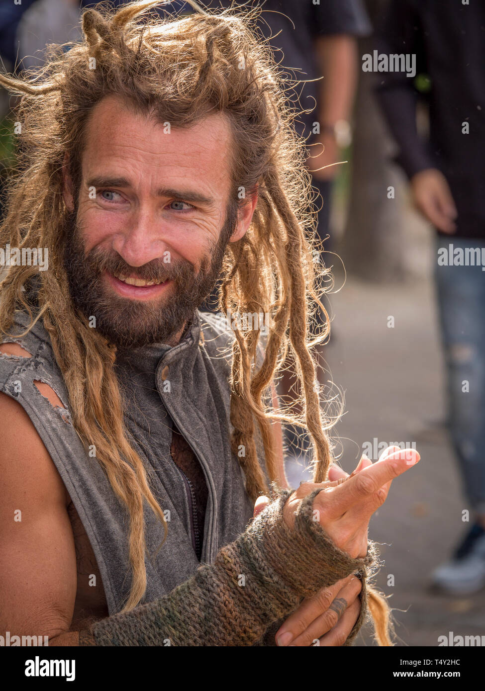 Tight Vertical portrait of young, bearded dreadlock street musician taking a break from playing piano with big smile on face. - Stock Image