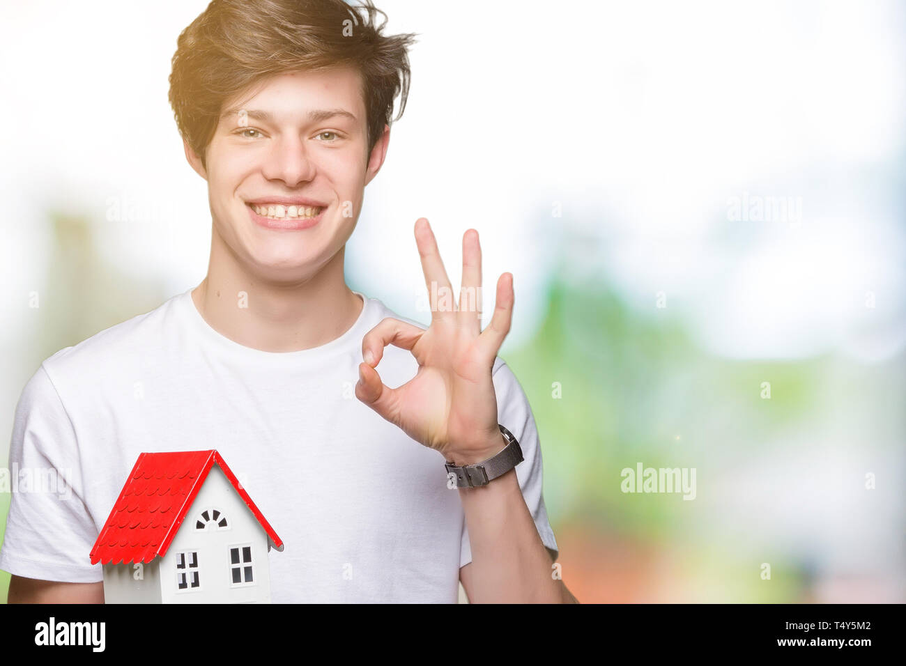 Young man holding house over isolated background doing ok sign with fingers, excellent symbol - Stock Image