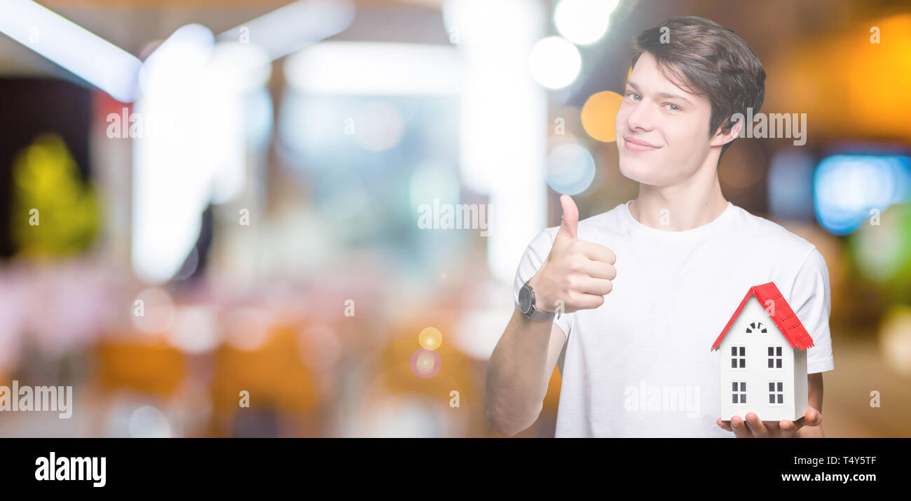 Young man holding house over isolated background happy with big smile doing ok sign, thumb up with fingers, excellent sign - Stock Image