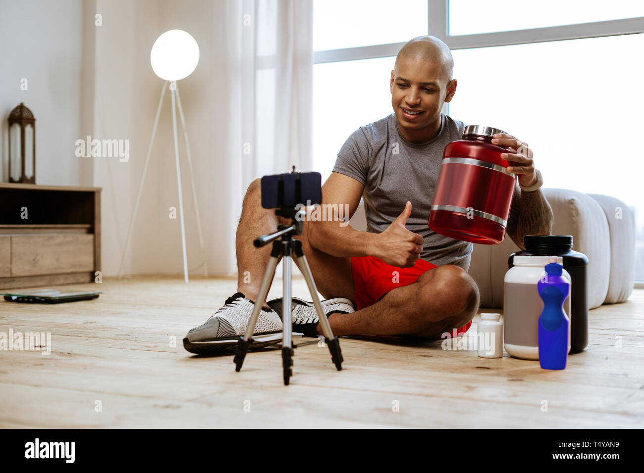 Sportsman sitting on the floor filming blog about dietary protein - Stock Image