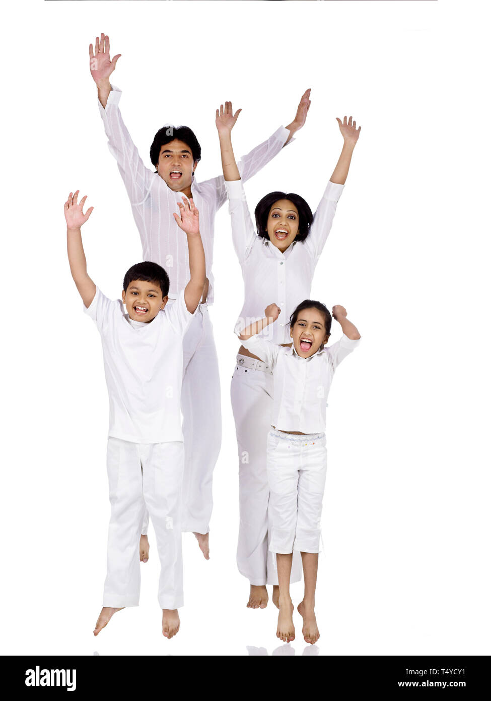 PORTRAIT OF FAMILY OF FOUR GRESSED IN WHITE JUMPING UP IN JOY - Stock Image