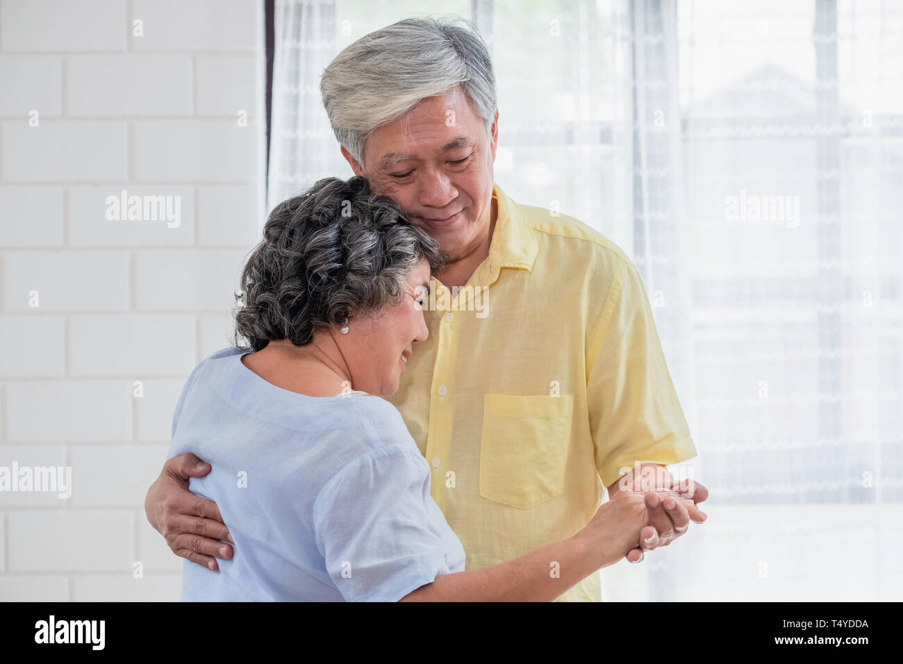 asian seniors couple enjoy dancing in living room at home.aging at home concept Stock Photo