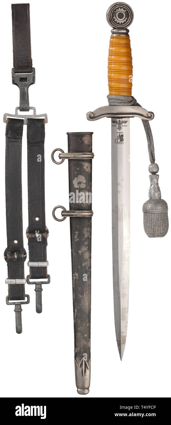 """A dagger M 38 for leaders, complete with service hanger and sword knot. The blade (minimally stained) with reverse Eickhorn logo and TeNo acceptance, obverse arms number """"2879"""". Silvered quillons and pommel with areas of patina, orange-coloured plastic grip. The scabbard (small dent) with mostly intact black toning, the locket with matching number """"2879"""". Length 41 cm. Complete with service hanger and belt loop of dark blue leather. historic, historical, technical, technic, emergency aid, object, objects, stills, clipping, clippings, cut out, cut-out, cut-outs, utensil, pie, Editorial-Use-Only Stock Photo"""