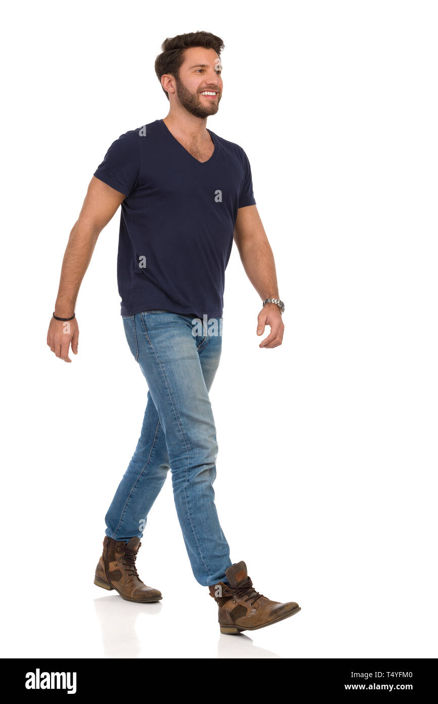 Happy man is walking in jeans, boots and blue t,shirt and
