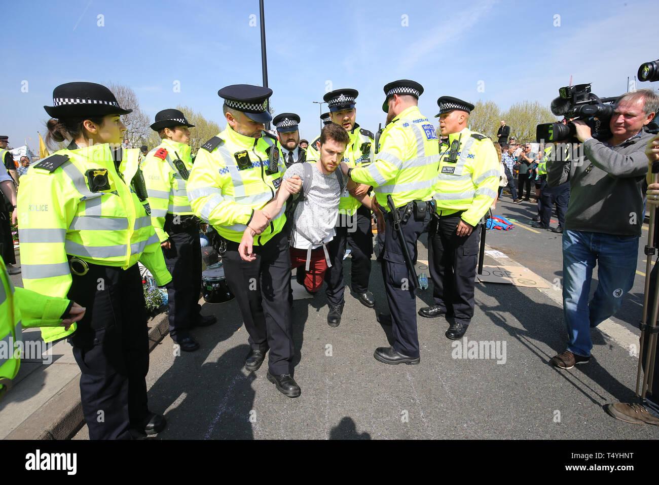 An Extinction Rebellion demonstrator is carried away by police on Waterloo Bridge in London. Stock Photo
