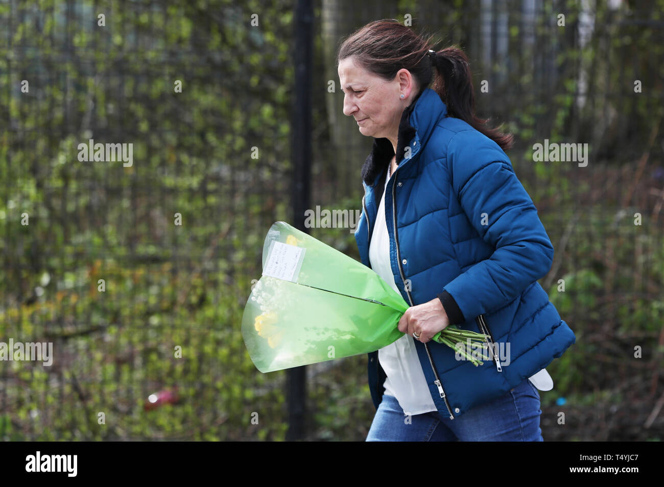 "A woman carries flowers to the scene in Londonderry, Northern Ireland, where 29-year-old journalist Lyra McKee was shot and killed when guns were fired and petrol bombs were thrown in what police are treating as a ""terrorist incident"". Stock Photo"
