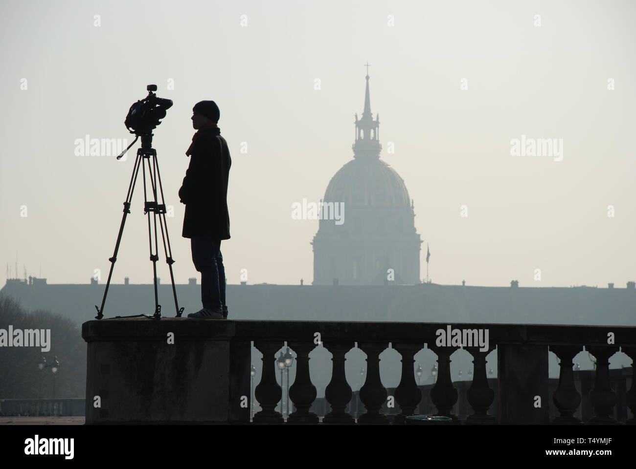 Taken while walking along the Seine in Paris. I spotted this videographer waiting for a vehicle driving past for a commercial. Stock Photo