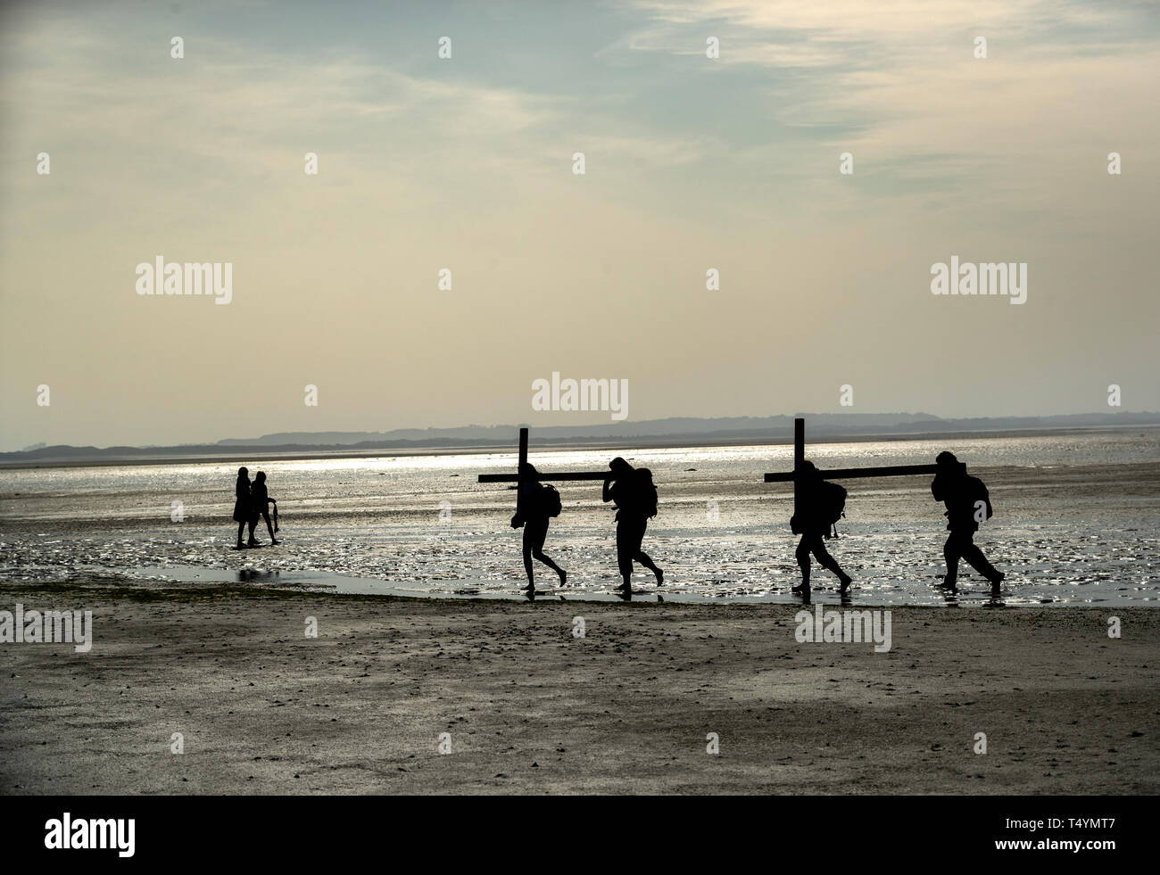 Pilgrims carrying crosses to the Holy Island of Lindisfarne in Northumberland during the annual Christian Easter pilgrimage on Good Friday. Stock Photo