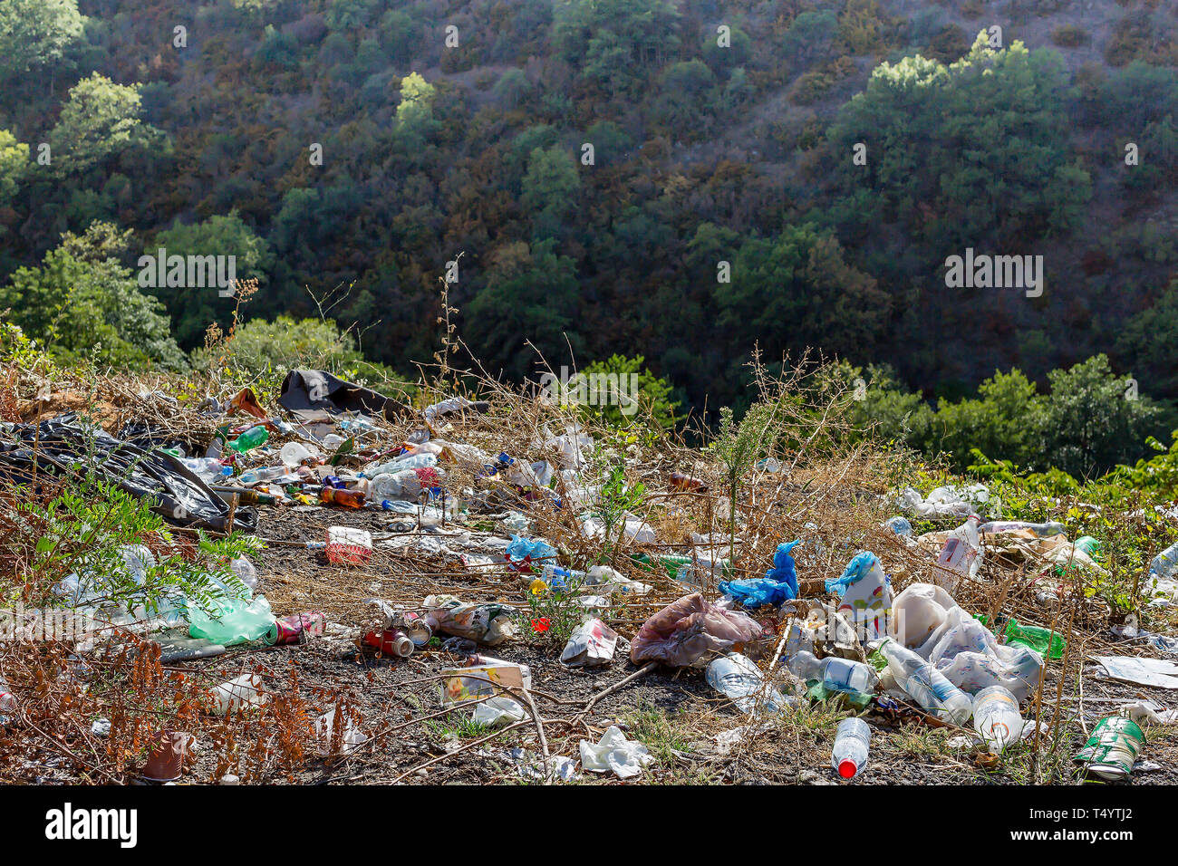 Plastic bottles, bags and other trash along the road. Trash at roadside. Concept of environmental pollution - Stock Image