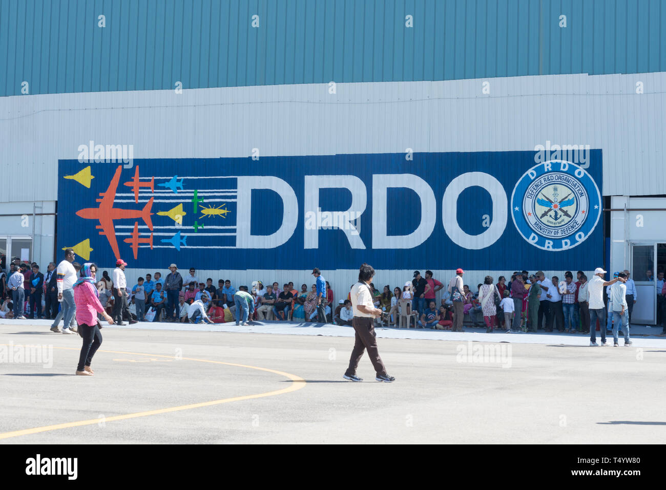 Bengaluru, India - February 22, 2019: Visitors at the Aero India 2019 rest from the shade outside the DRDO hall. Aero India is a biennial air show and - Stock Image