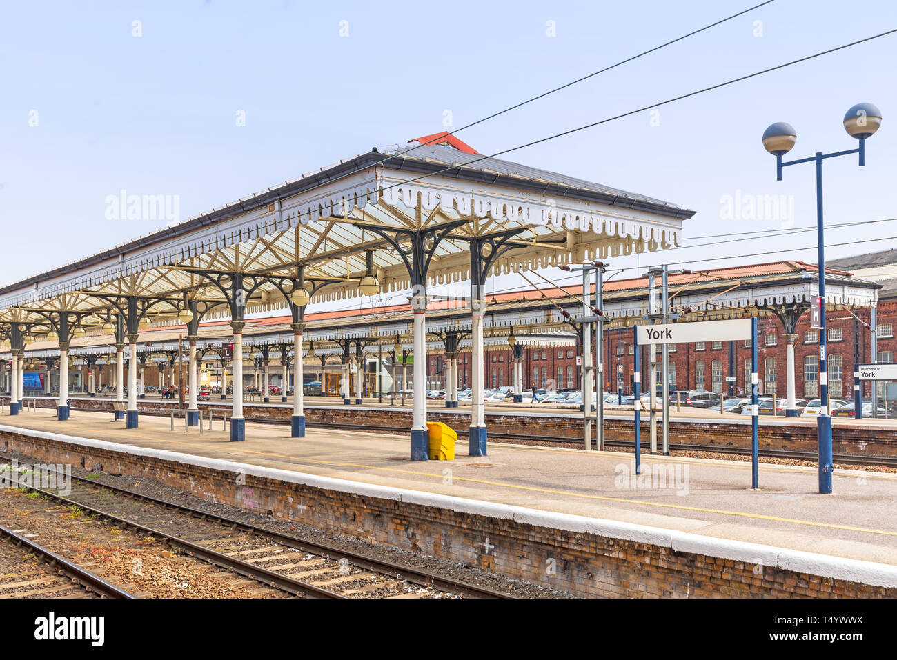 York railway station platform with elaborate 19th Century canopies.  A building and car park lies beyond.  A blue sky is overhead. - Stock Image