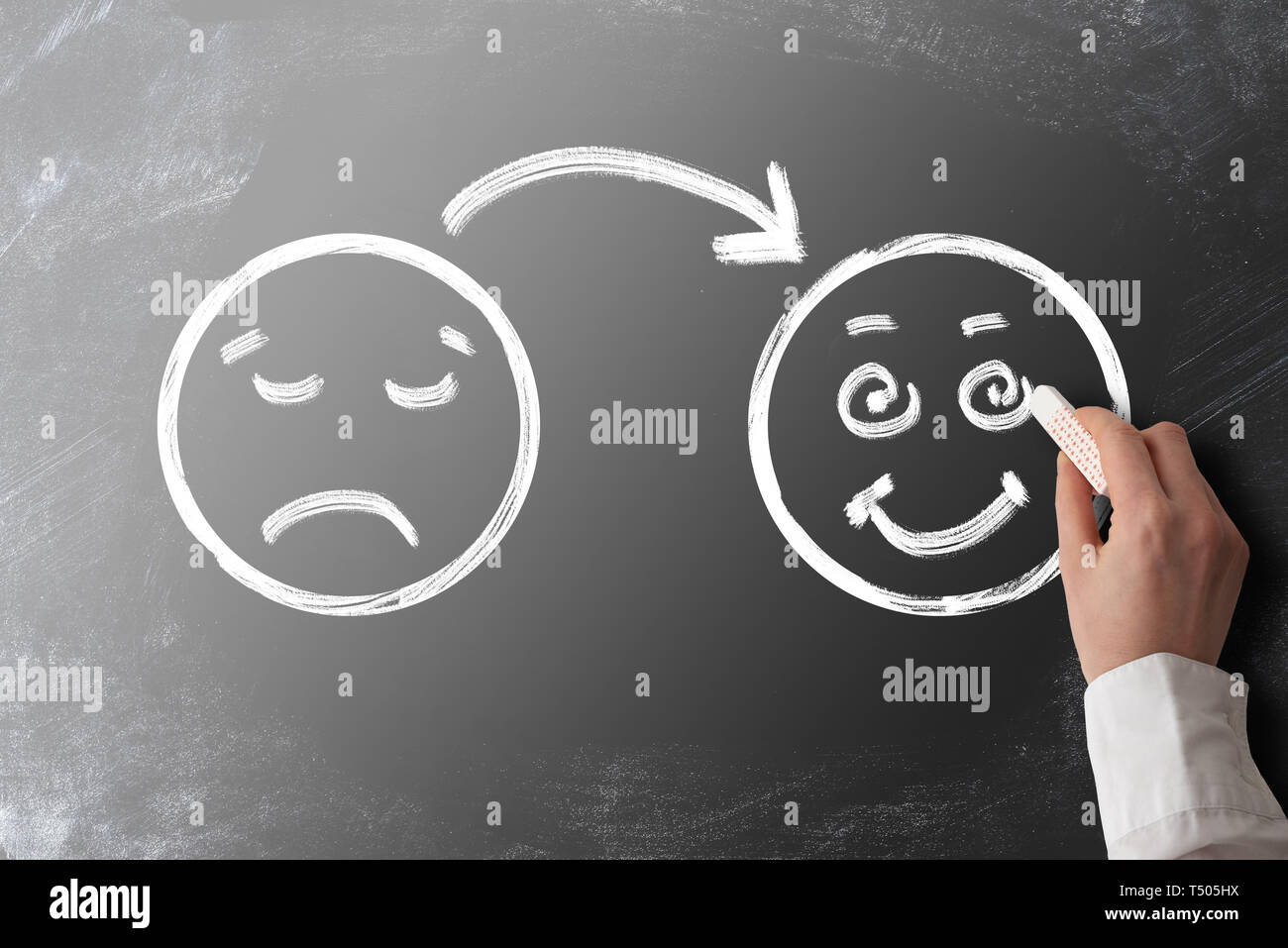 client or customer satisfaction concept with chalk drawing of sad face turning into smiling face on blackboard - Stock Image