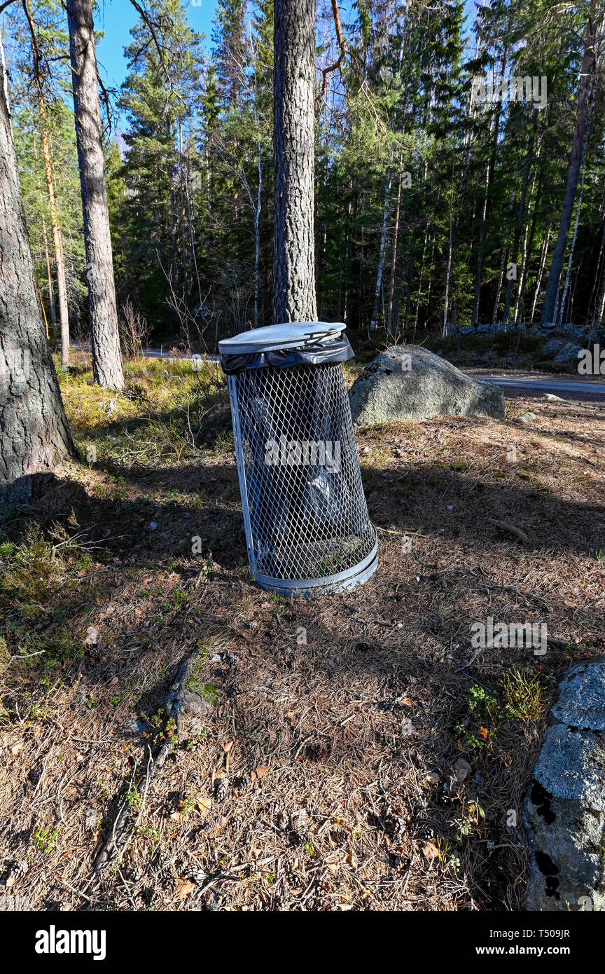 Garbage can near a little lake in Sweden - Stock Image