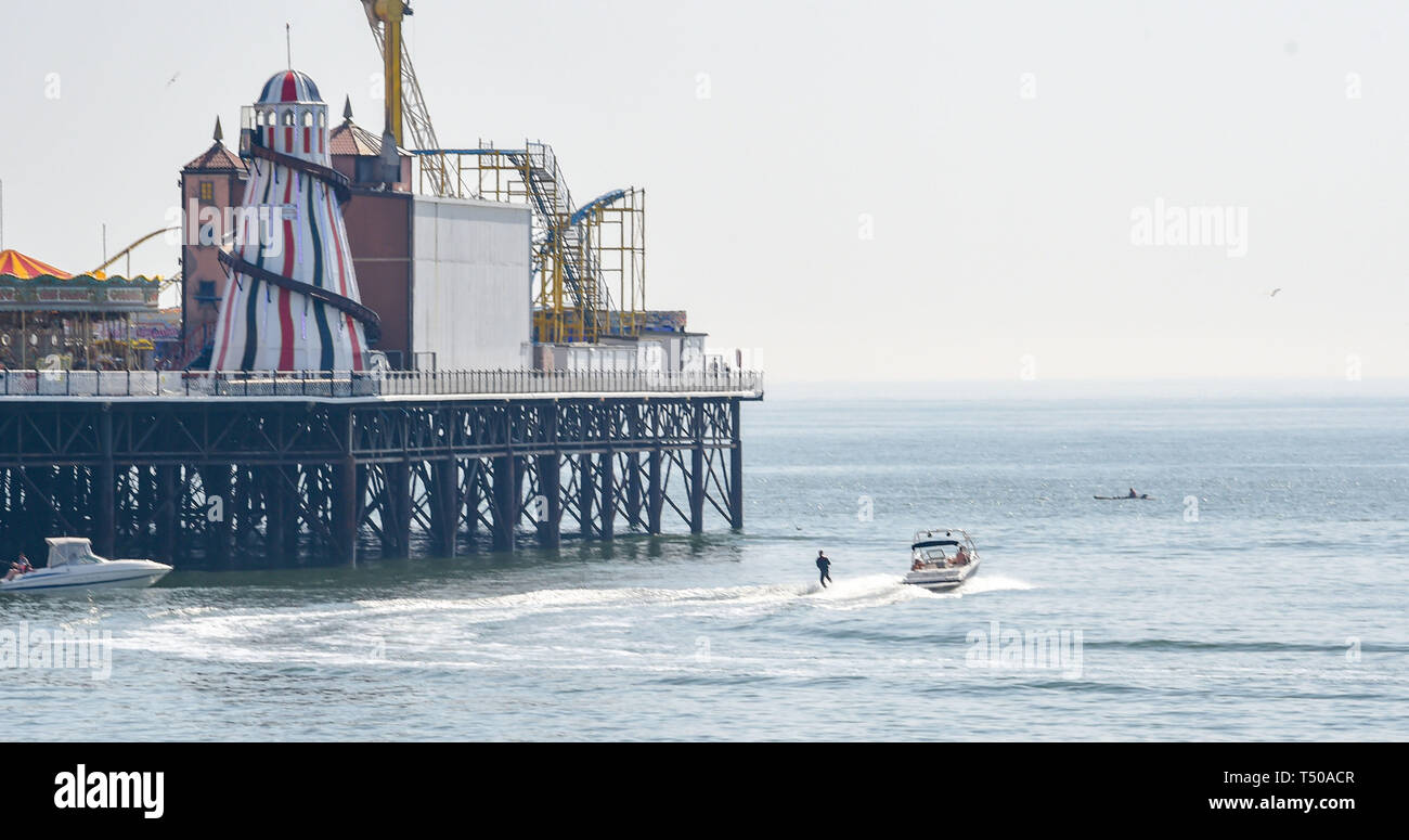 Brighton, UK. 19th Apr, 2019. A water skier heads around Brighton Palace Pier as visitors flock to the seaside to enjoy the Good Friday sunshine as temperatures reach the mid twenties along the South Coast Credit: Simon Dack/Alamy Live News Stock Photo