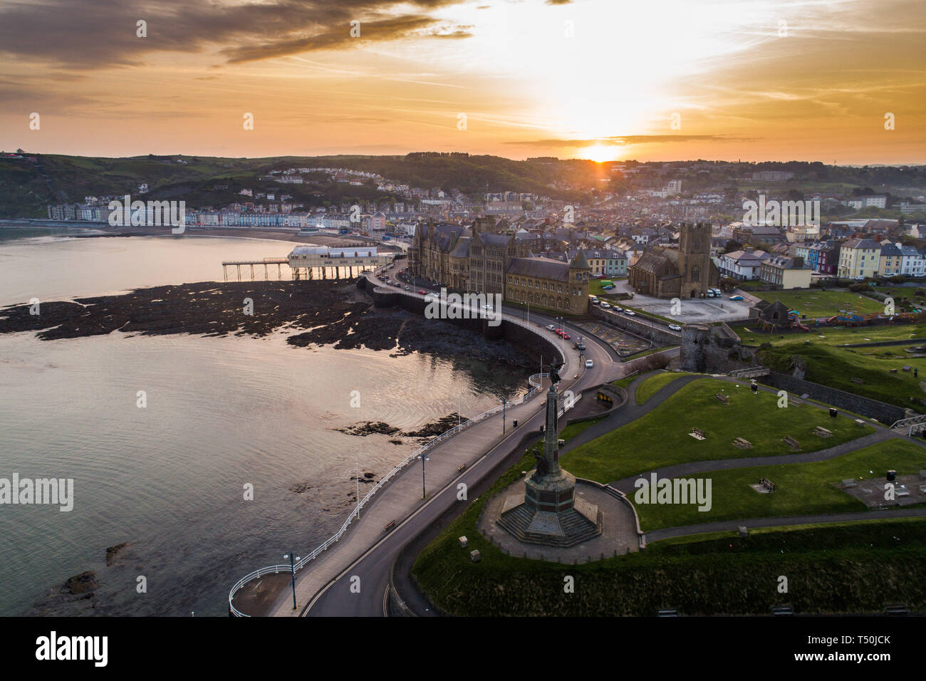 Aberystwyth Wales UK, Easter Saturday, 20 April 2019. UK Weather: Daybreak over the seaside and university town of Aberystwyth on the west wales coast, at the start of Easter Saturday 2019. The weather is again set to be hot and sunny, with temperatures in the low 20's Celsius (low 70's Fahrenheit). Aerial image by CAA approved and licenced drone operator photo Credit: Keith Morris/Alamy Live News - Stock Image