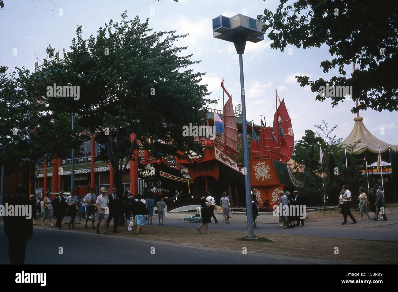 People walking on a sidewalk near mock Chinese junks that formed part of the Hong Kong Pavilion during the New York World's Fair, Flushing Meadows Park, Queens, NY, June 1964. () Stock Photo