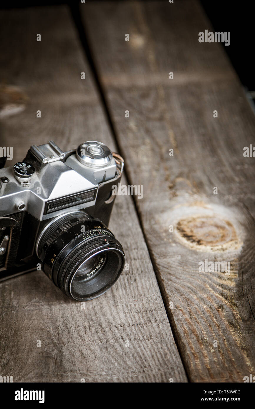 Old vintage photo camera with black background on a wooden table - Stock Image