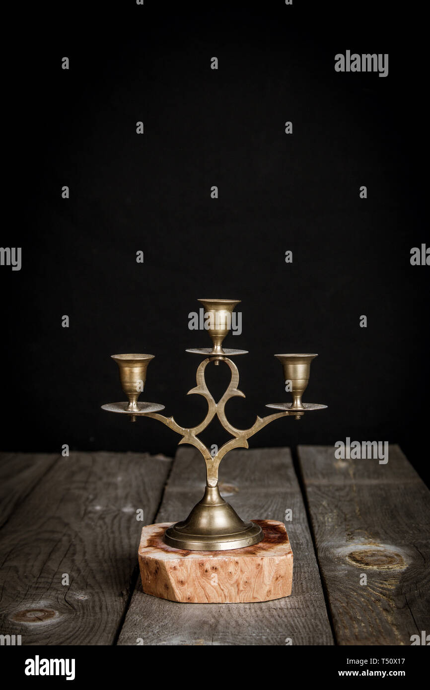 Rustic candlestick with black background on a wooden table - Stock Image