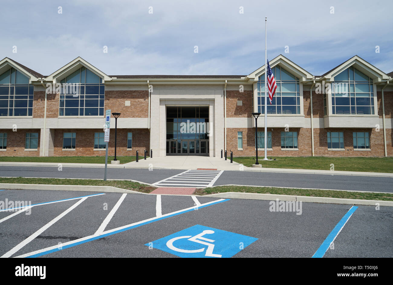Exterior of a modern American school.   The school is two story and there is an American flag on the flagpole.  This is Northampton Area Middle School - Stock Image