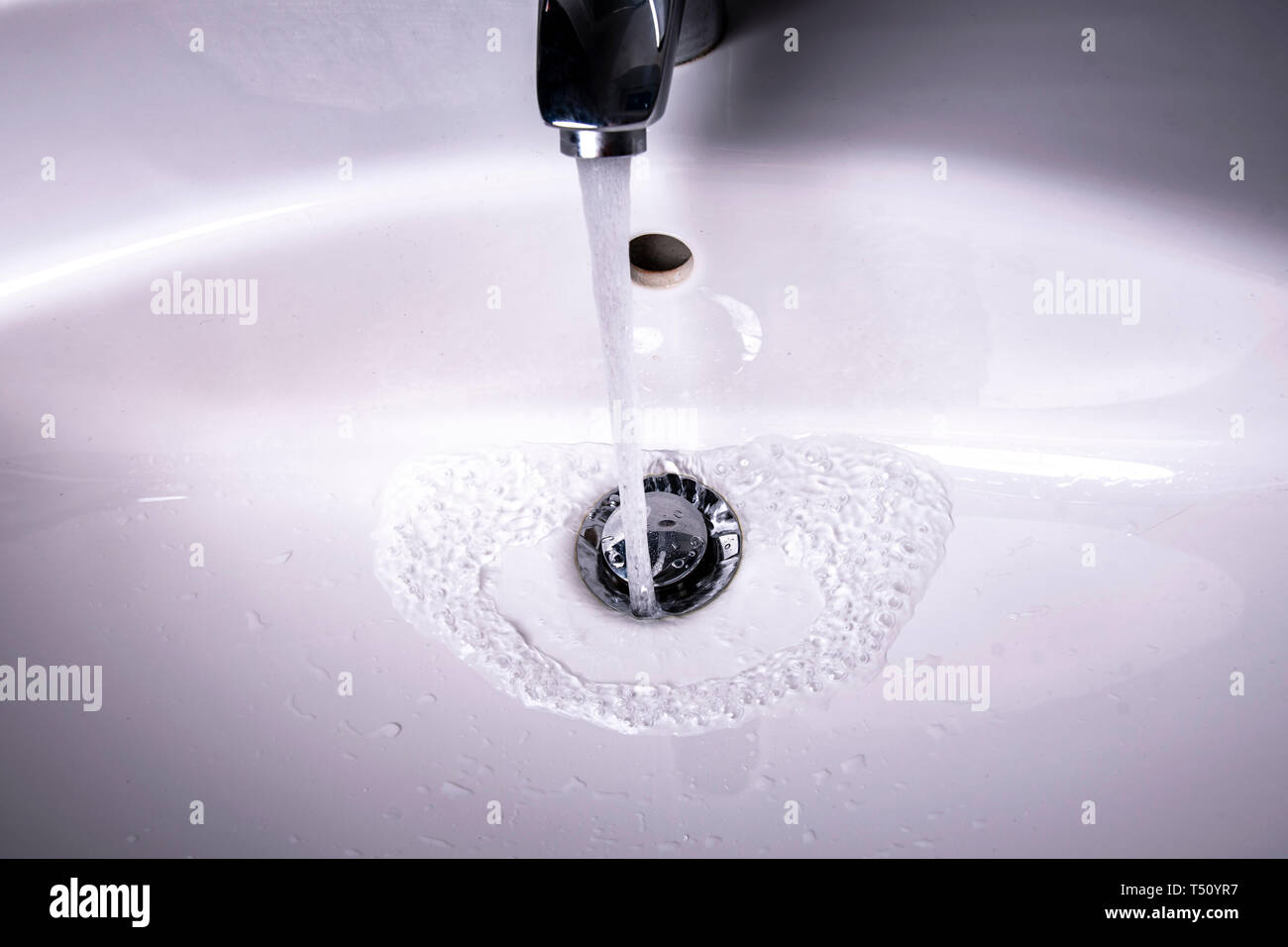 Water flows into the sink with drain plug Stock Photo